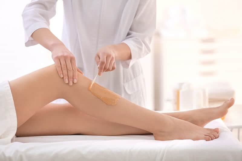 A female's legs being waxed